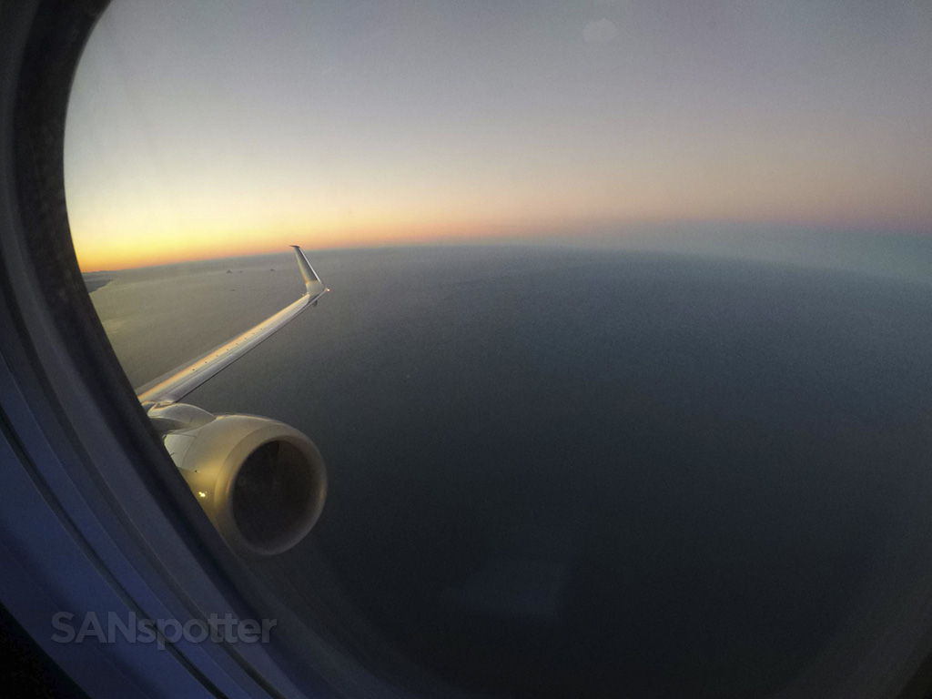 united 737-900 flying over pacific ocean